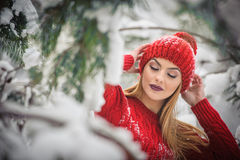 Beautiful woman in red with brown fur cape enjoying the winter scenery in forest. Blonde girl posing under snow-covered branches Stock Image