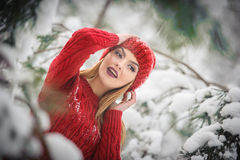 Beautiful woman in red with brown fur cape enjoying the winter scenery in forest. Blonde girl posing under snow-covered branches Stock Images
