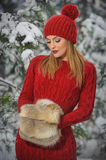 Beautiful woman in red with brown fur cape enjoying the winter scenery in forest. Blonde girl posing under snow-covered branches Royalty Free Stock Images