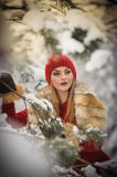 Beautiful woman in red with brown fur cape enjoying the winter scenery in forest. Blonde girl posing under snow-covered branches Royalty Free Stock Photography