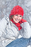 Beautiful woman with red cap on the snow day. stock photo