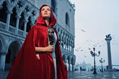 Beautiful woman in red cloak. Against Dodge's Palace royalty free stock image