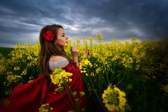 Beautiful woman with red cloak on blooming rapeseed field Royalty Free Stock Images