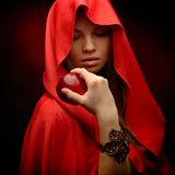 Beautiful woman with red cloak hoding apple Royalty Free Stock Photos