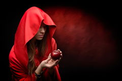 Beautiful woman with red cloak hoding apple Royalty Free Stock Photography