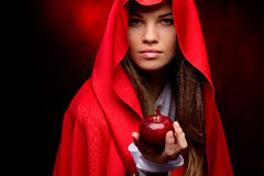 Beautiful woman with red cloak holding apple Stock Photos