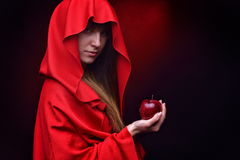Beautiful woman with red cloak holding apple Royalty Free Stock Photos