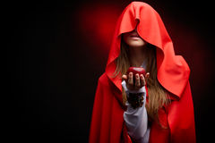 Beautiful woman with red cloak holding apple Stock Photo