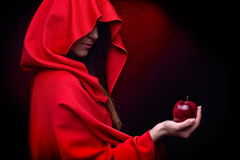 Beautiful woman with red cloak holding apple Royalty Free Stock Photo