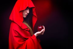 Beautiful woman with red cloak holding apple Stock Image