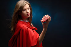 Beautiful woman with red cloak holding pomegranate Stock Image