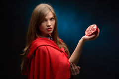 Beautiful woman with red cloak holding pomegranate Stock Photography