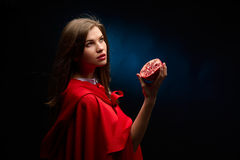Beautiful woman with red cloak holding pomegranate Royalty Free Stock Image