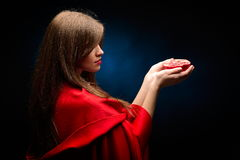 Beautiful woman with red cloak holding pomegranate Stock Photos