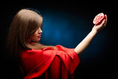 Beautiful woman with red cloak holding pomegranate Royalty Free Stock Images