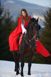 Beautiful woman with red cloak with horse outdoor. In winter stock photo