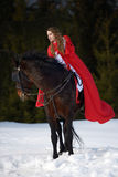 Beautiful woman with red cloak with horse outdoor. In winter royalty free stock photo