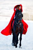 Beautiful woman with red cloak with horse outdoor in winter. Beautiful woman with red cloak riding horse outdoor in winter stock photo