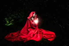 Beautiful woman with red cloak and lantern in the woods. By night stock photos