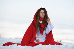 Beautiful woman with red cloak sitting on the snow Royalty Free Stock Photo