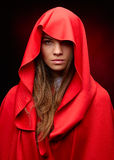 Beautiful woman with red cloak. In studio royalty free stock photo