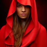 Beautiful woman with red cloak. In studio stock image