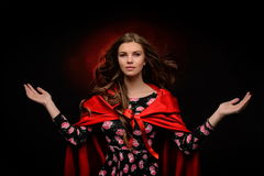 Beautiful woman with red cloak in studio Stock Image