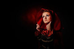 Beautiful woman with red cloak in studio Royalty Free Stock Image