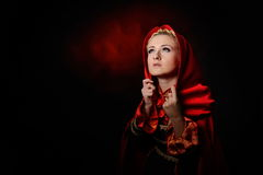 Beautiful woman with red cloak in studio Stock Photo