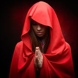Beautiful woman with red cloak in studio. Praying royalty free stock image