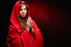 Beautiful woman with red cloak in studio praying Stock Image