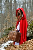 Beautiful woman with red cloak and suitcase Stock Images