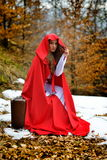 Beautiful woman with red cloak and suitcase alone Stock Images