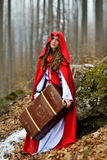 Beautiful woman with red cloak and suitcase Stock Photo