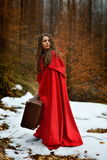 Beautiful woman with red cloak and suitcase alone in the woods Stock Photos