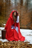 beautiful woman with red cloak and suitcase in the woods Royalty Free Stock Image