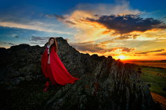 Beautiful woman with red cloak in the sunset light Royalty Free Stock Images