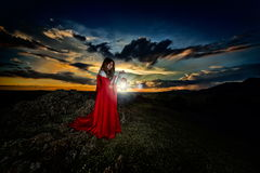 Beautiful woman with red cloak in the sunset light. In spring royalty free stock photos