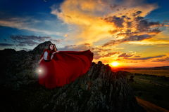 Beautiful woman with red cloak in the sunset light Stock Photography