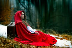 Beautiful woman with red cloak in the woods Stock Images