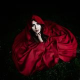 Beautiful woman with red cloak in the woods. In spring royalty free stock images