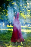 Beautiful woman with red cloak  in the woods Stock Photo