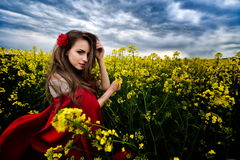 Beautiful woman with red cloak in yellow blooming field. Beautiful woman with red cloak on blooming rapeseed field in summer stock photos