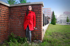 Beautiful woman in a red coat on a brick wall in the city royalty free stock images