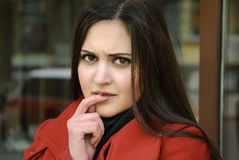 Beautiful woman in red coat and her serious look Stock Photo