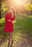 Beautiful woman in red coat posing in autumn Park stock photography