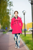 Beautiful woman in red coat walking autumn street Royalty Free Stock Photography
