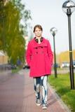 Beautiful woman in red coat walking autumn street Royalty Free Stock Photos