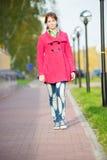 Beautiful woman in red coat walking autumn street Stock Photo