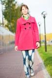 Beautiful woman in red coat walking autumn street Stock Photography